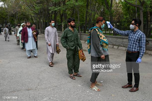 Health worker checks the body temperature of devotees as a preventive measure against the COVID-19 coronavirus before the Friday prayers on the first...