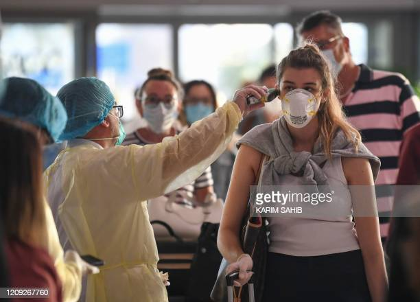 Health worker checks the body temperature of passengers bound for Frankfurt at Dubai International Airport on April 6 as Emirates Airline resumed a...