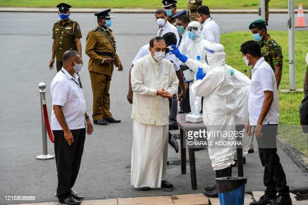 A health worker checks the body temperature of Sri Lanka's former speaker of the Parliament Karu Jayasuriya as he arrives to attend a laying in state...