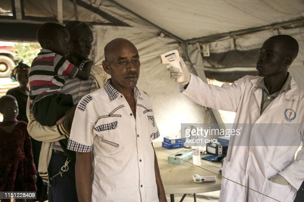 Health worker checks the fever of travellers coming across South Sudan's Nimule border town from Uganda on June 19 following recent deaths from Ebola...