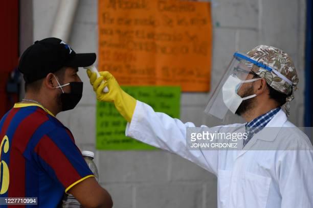 Health worker checks the temperature of a customer at La Asuncion market in Villa Nueva, 20 km south Guatemala City on July 20, 2020.
