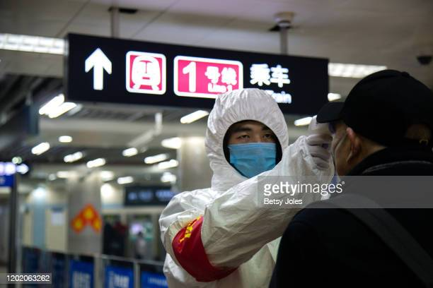 A health worker checks the temperature of a man entering the subway on January 26 2020 in Beijing China The number of cases of coronavirus rose to...