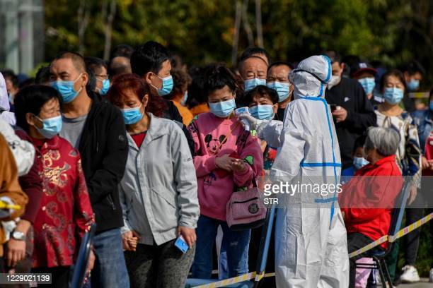 Health worker checks the temperature of residents as they line up to be tested for the COVID-19 coronavirus in Qingdao, in China's eastern Shandong...
