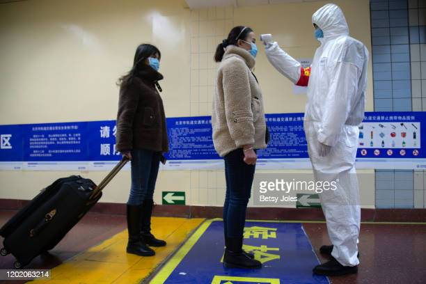 A health worker checks the temperature of women entering the subway on January 26 2020 in Beijing China The number of cases of coronavirus rose to...