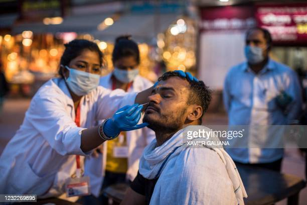 Health worker collects a nasal swab sample from a Hindu devotee to test for the Covid-19 coronavirus during the ongoing religious Kumbh Mela festival...