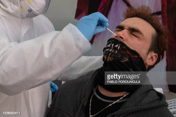 A health worker collects a nasal swab sample from a passenger to be tested for COVID19 before he is allowed to board a ferry to Buenos Aires at...