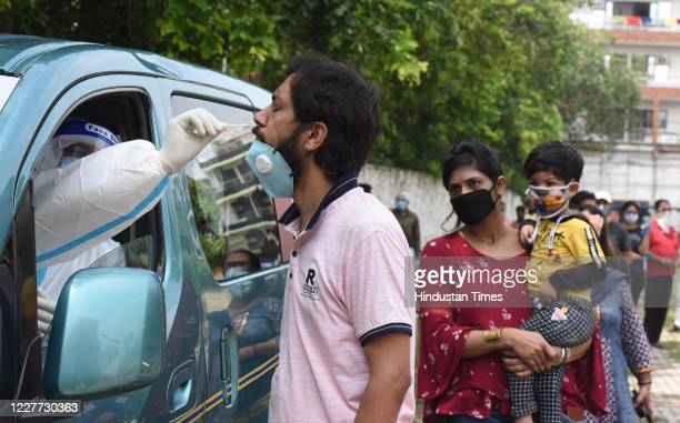 Health worker collects a swab sample from a man to test for Covid-19 infection at Ramlila Maidan, in Adarsh Nagar, on July 21, 2020 in New Delhi,...