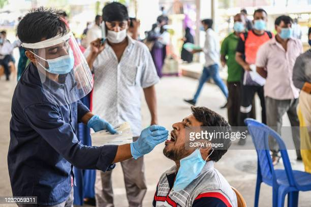 Health worker collects a swab sample from a man to test for the COVID-19 coronavirus at Mugda Medical College and Hospital. Mugda Medical College and...