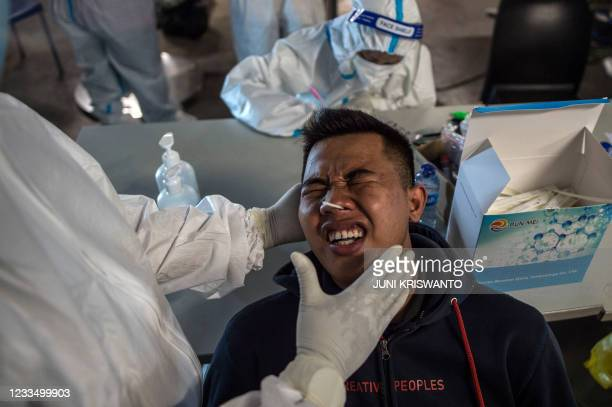 Health worker collects a swab sample from a shopper to test for the Covid-19 coronavirus before he is allowed to enter a shopping mall in Surabaya on...