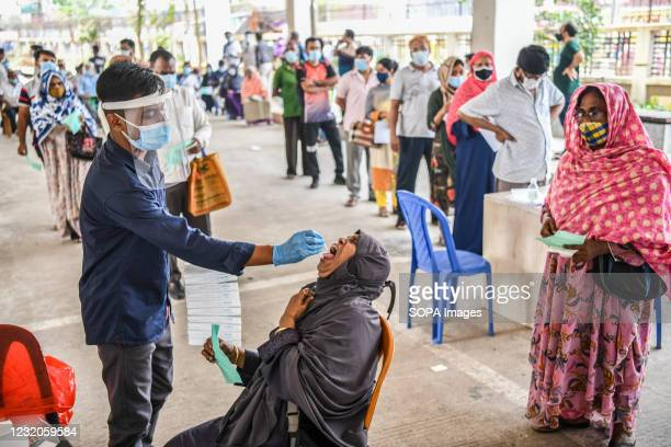 Health worker collects a swab sample from a woman to test for the COVID-19 coronavirus at Mugda Medical College and Hospital. Mugda Medical College...
