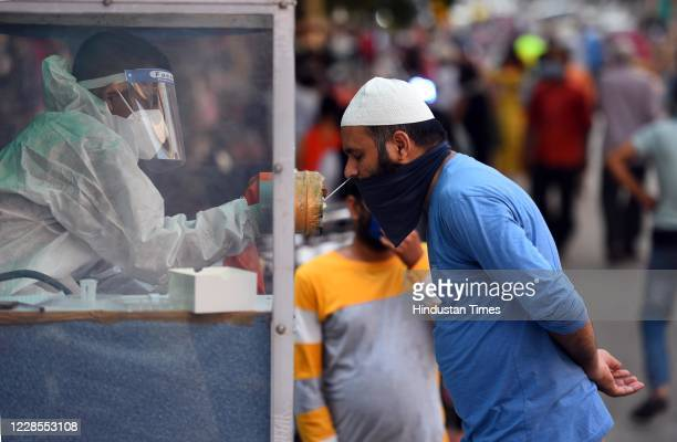 A health worker collects a swab sample to test for Covid19 infection at a weekly market in Pandav Nagar on September 16 2020 in New Delhi India