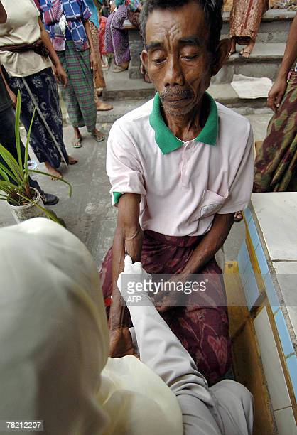 Health worker collects blood sample from a relative of Ayu Srinadi, who died 21 August 2007, for tests in Tabanan on Bali island, 22 August 2007....