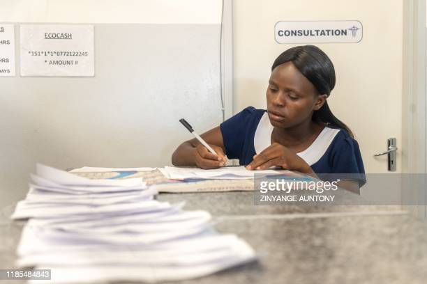 Health worker compile a list of patients to be attended to at the West Memorial Clinic in the Cowdray Park township, Bulawayo, in Zimbabwe on...