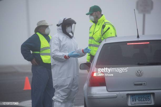 A health worker directs motorists at a coronavirus drive thru testing location operated by Murphy Medical Associates at Cummings Park on March 20...