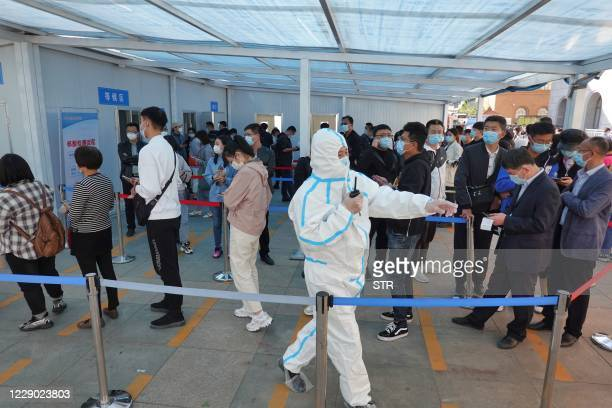 Health worker directs people as they line up to be tested for the COVID-19 coronavirus in Yantai, in China's eastern Shandong province on October 12...