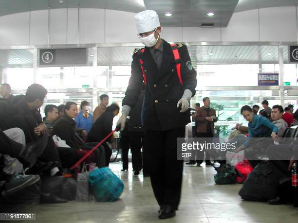 A health worker disinfecting a bus station in Harbin northeastern China's Heilongjiang province 21 April 2003 Drastic Chinese measures designed to...
