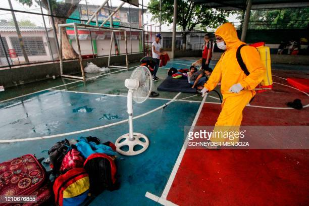 A Health worker disinfects a multisports court in the Colombian town of Puerto Santander in the Norte de Santander Department on the border with...