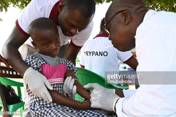 Health worker draws blood from a child with a syringe as she takes part in an Human African Trypanosomiasis, also known as sleeping sickness,...