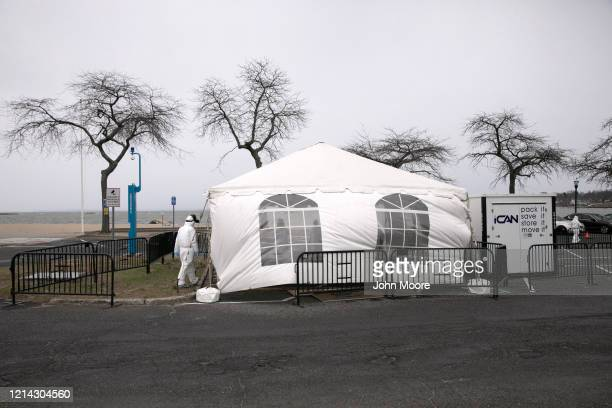 Health worker dressed in personal protective equipment awaits new patients a drive-thru coronavirus testing station at Cummings Park on March 23,...