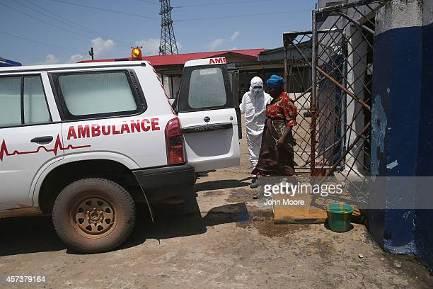 A health worker escorts a woman from a holding center into an ambulance for transport to an Ebola treatment center in the West Point neighborhood on...