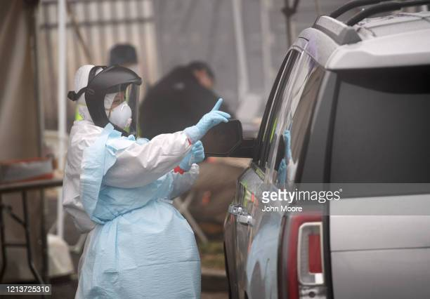 A health worker explains a coronavirus test before administering the it to a motorist at a drive thru testing location operated by Murphy Medical...