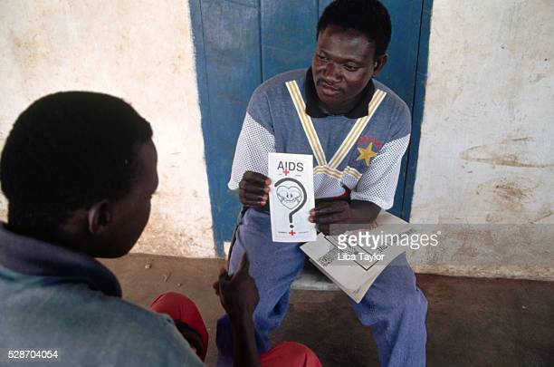 Health Worker Explains AIDS Awareness Leaflet in The Gambia