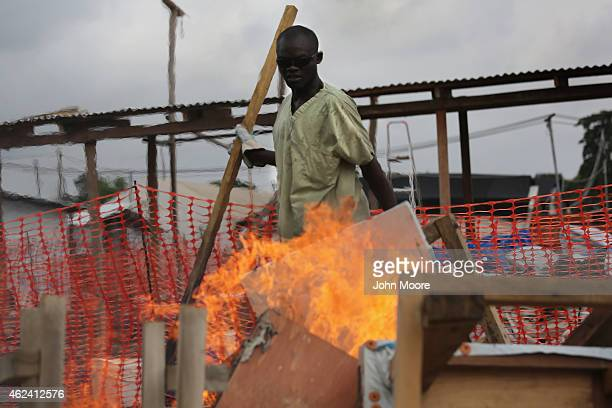 A health worker from Doctors Without Borders lights fire to materiel from from the Ebola Treatment Unit on January 26 2015 in Paynesville Liberia MSF...