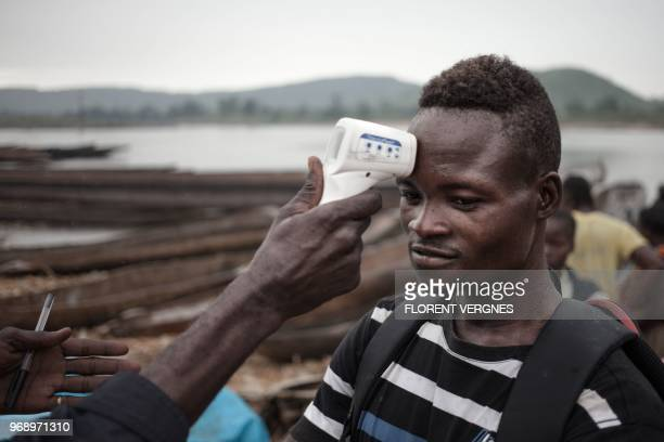 A health worker from the Ministry of Health monitors the temperature of a young traveller from the Democratic Republic of Congo at each port in...