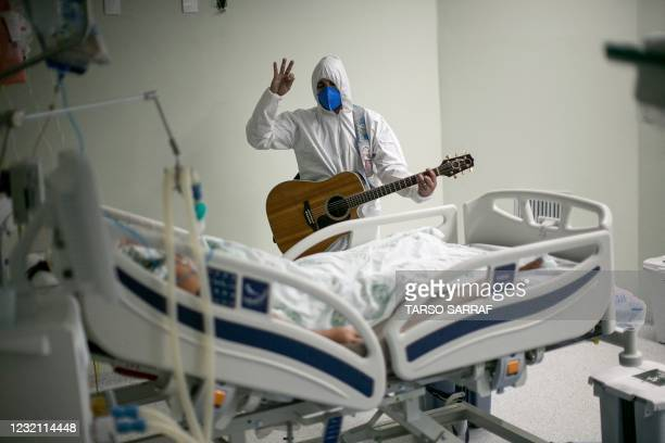 Health worker from the Portuguese charity hospital in Belem, Para State, Brazil, sings and prays for a COVID-19 patient inside the hospital wards and...