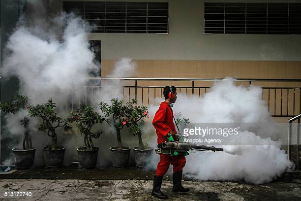 A health worker fumigates a school to prevent the spreading of the dengue fever by mosquitoes in Surakarta Central Java Indonesia on March 01 2016