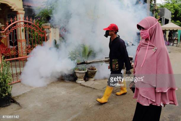 A health worker fumigation densely populated areas to prevent the spread of Aedes aegypti in an attempt to control dengue fever at a neighborhood in...
