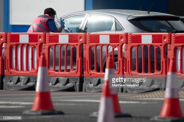 Health worker gestures to a person in a car at the coronavirus drive-through testing centre at the Cardiff City stadium on April 23, 2020 in Cardiff,...