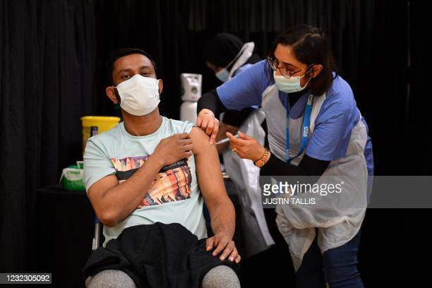 Health worker gives an injection of the Astrazeneca/Oxford Covid-19 vaccine at a temporary vaccination centre set up at the East London Mosque in...