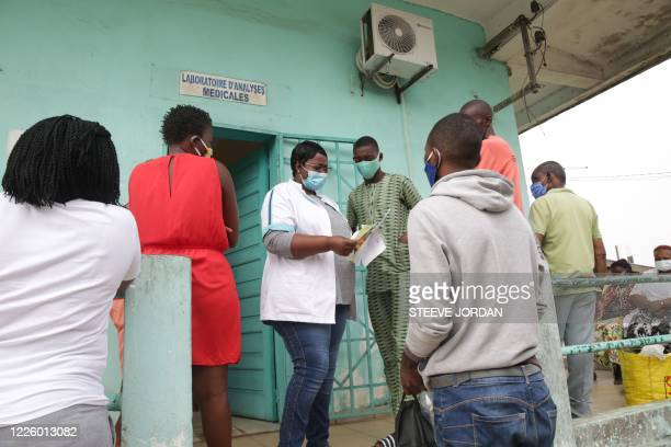 Health worker hands patients their COVID-19 coronavirus test results back at the Nkembo health centre in Libreville on July 9, 2020 after they got...