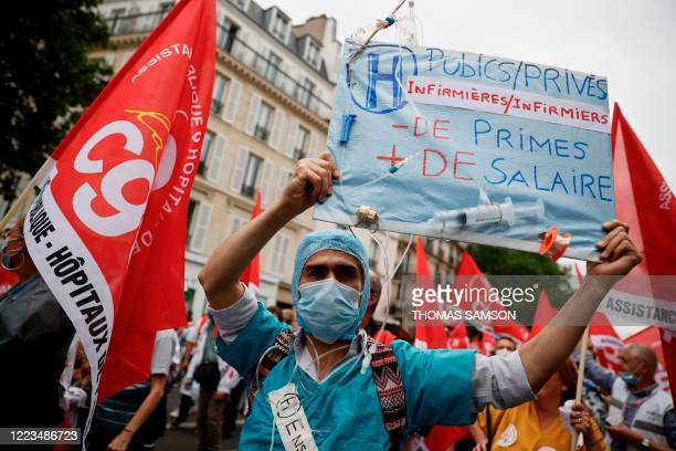 """Health worker holds a placard reading """"Public/Private hospitals - less bonus more wage"""" as they attend a demonstration, as part of a nationwide day..."""