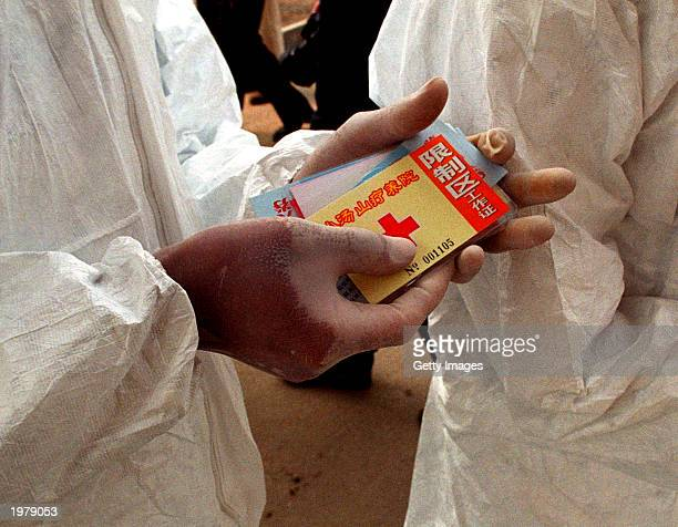 A health worker holds passes needed to gain access to the restricted area of the Xiaotangshan hospital that's for medics and patients only and which...