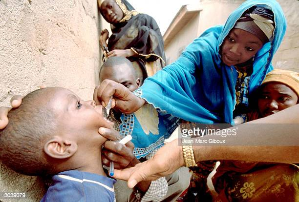 Health worker immunize a child against polio in the street of the old city of Kano during the National Immunization Days November 13, 2002 in...