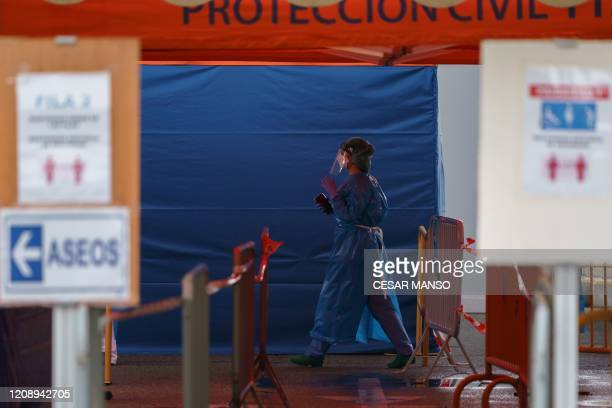 A health worker in full protective gear walks at the external screening area of the Burgos Hospital set up in order to separate patients with...