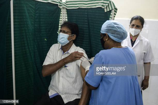 Health worker inoculates a catholic priest with a dose of the Covaxin vaccine against the Covid-19 coronavirus during a vaccination drive at a health...