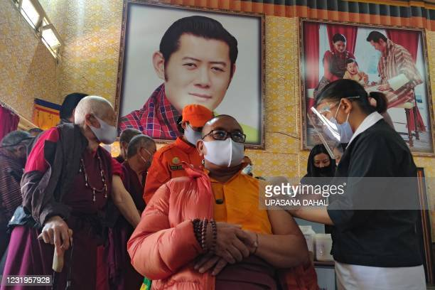 Health worker inoculates a dose of a COVID-19 coronavirus vaccine to a Buddhist monk sitting in front of a portrait of Bhutan's King Jigme Khesar...
