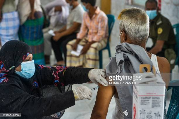 Health worker inoculates a man with the jab of Sinopharm Covid-19 coronavirus vaccine during a mass vaccination camp at Kholamora in Keraniganj on...
