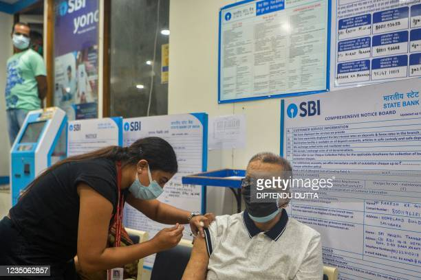 Health worker inoculates an elderly man with the jab of Covishield vaccine against the Covid-19 coronavirus at a branch of State Bank of India in...