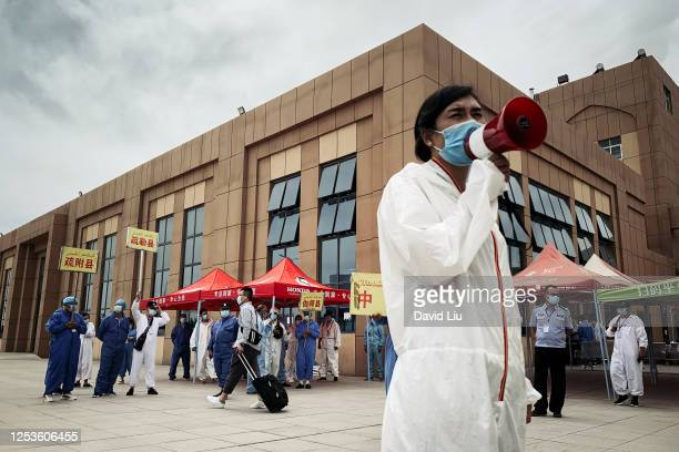 KASHGAR CHINA JUNE 30 2020 A health worker is leading arriving passengers to their correct registries at Kashgar Railway Station on June 30 2020 in...