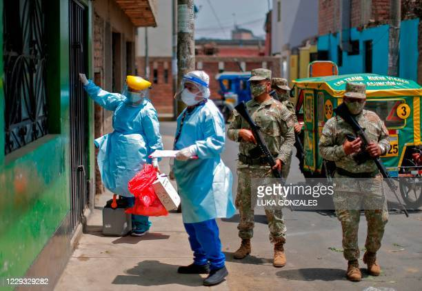 Health worker knocks the door of a house next to soldiers during a preventive vaccination campaign against diphtheria in Lima, on October 28 after a...