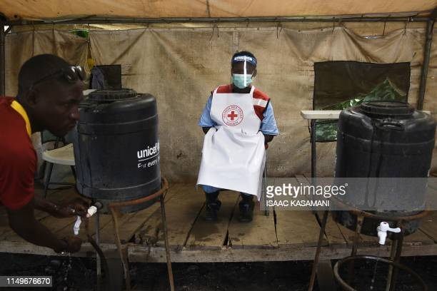 TOPSHOT A health worker monitors to ensures that people wash their hands at the Mpondwe Health Screening Facility in the Uganda border town with the...