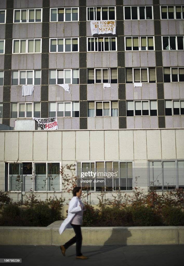 A health worker passes by La Paz hospital where banners hang from the windows on November 21, 2012 in Madrid, Spain. Doctors and nurses in the Spanish capital are preparing for a four day strike to protest against the privatisation of some parts of Spain's national health service.