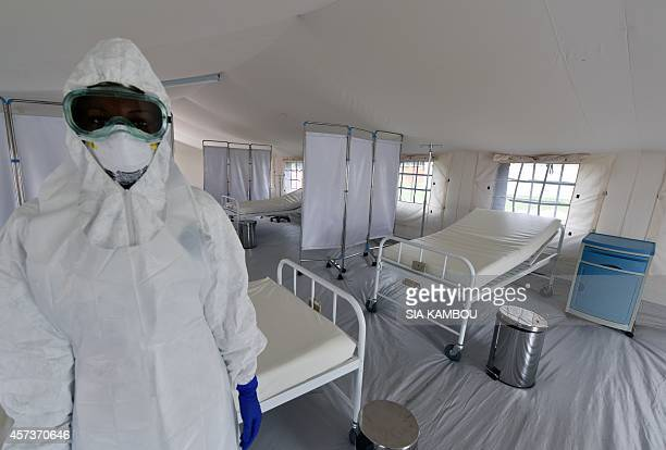 A health worker poses inside a tent in the Ebola treatment unit being preventively set to host potential Ebola patients at the University Hospital of...