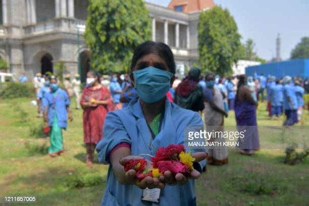 Health worker poses with flower petals she collected after an Indian Air Force Mi-17 helicopter dropped them over the Victoria Hospital to pay...