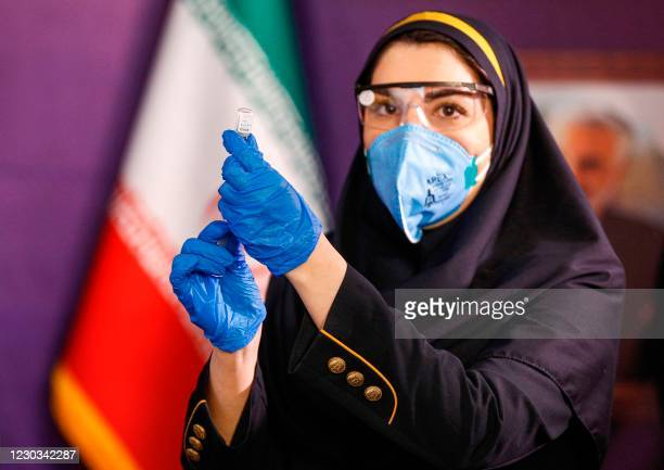 Health worker prepares an injection for a woman during the first trial phase of a locally-made Iranian vaccine for COVID-19 coronavirus disease in...