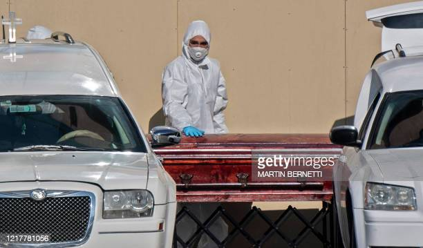 Health worker pushes a casket outside the San Jose public hospital morgue, amid the spread of the coronavirus disease in Santiago, on June 05, 2020....